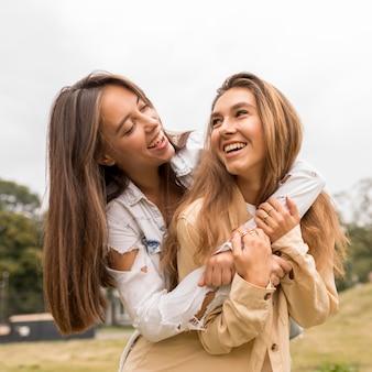 Szczęśliwi przyjaciele przytulanie na zewnątrz