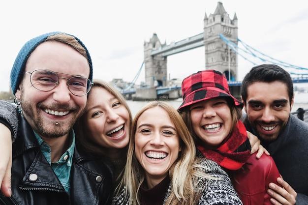 Szczęśliwi przyjaciele robią sobie zdjęcie selfie w londynie z tower bridge