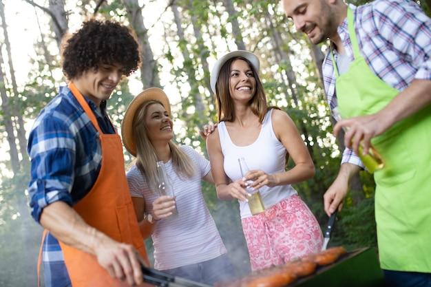 Szczęśliwi przyjaciele robiący grilla i jedzący obiad na łonie natury