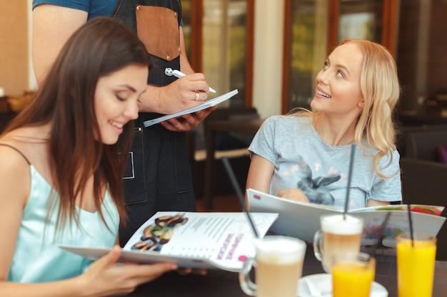 Szczęśliwi przyjaciele rozmawiają, patrząc na siebie, siedząc w barze z kelnerem