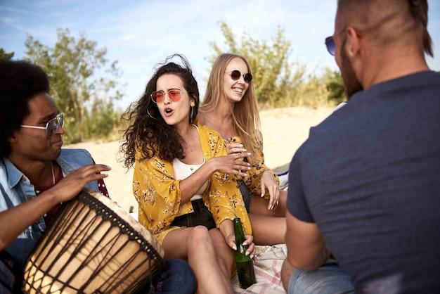 Szczęśliwi Przyjaciele Siedzący Na Plaży Z Instrumentami Muzycznymi Premium Zdjęcia