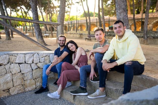 Szczęśliwi przyjaciele siedzący na schodach parku z sosnami patrzą na aparat z uśmiechem