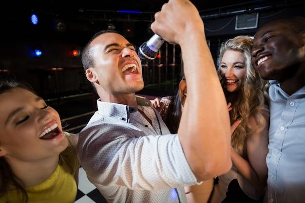 Szczęśliwi przyjaciele śpiewają na karaoke