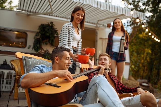 Szczęśliwi przyjaciele śpiewają piosenki z gitarą na pikniku na kempingu w lesie. młodzież przeżywa letnią przygodę na kamperze, samochodzie kempingowym dwie pary odpoczywa, podróżuje z przyczepą