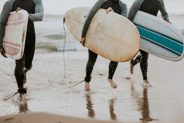 Szczęśliwi przyjaciele surfujący na plaży
