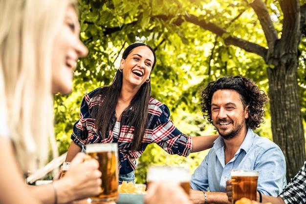 Szczęśliwi przyjaciele świętuje picie kufel piwa w parku na świeżym powietrzu - młodzi ludzie rozmawiają i śmieją się razem w ogrodzie pubu browaru - koncepcja przyjaźni, młodzieży i napojów