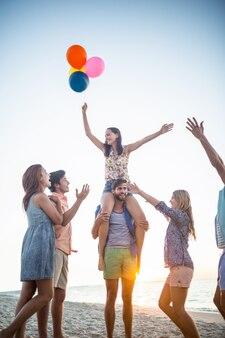 Szczęśliwi przyjaciele tanczy na piasku z balonem