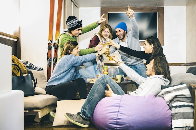 Szczęśliwi przyjaciele tosty i piją piwo w schronisku po nartach