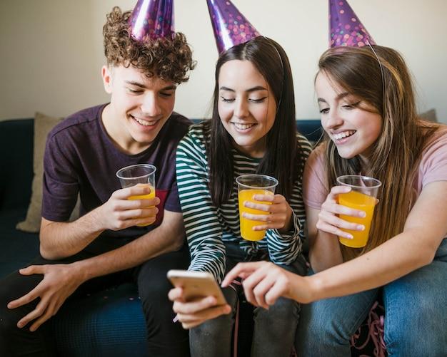 Szczęśliwi przyjaciele trzyma filiżanki sok