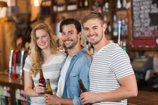 Szczęśliwi przyjaciele trzyma piwne butelki przy pubem
