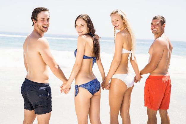 Szczęśliwi przyjaciele trzyma ręki wpólnie na plaży