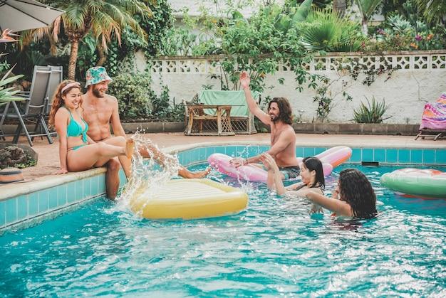 Szczęśliwi przyjaciele unosi się z air lilo piłką na imprezie przy basenie - młodzi ludzie dobrze się bawią na wakacjach