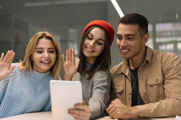 Szczęśliwi przyjaciele używa cyfrową pastylkę do wideokonferencji