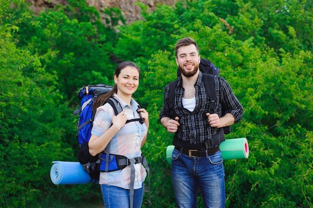 Szczęśliwi przyjaciele w trawy i niebieskiego nieba tle, relaksują czas na wakacje, pojęcie podróż.
