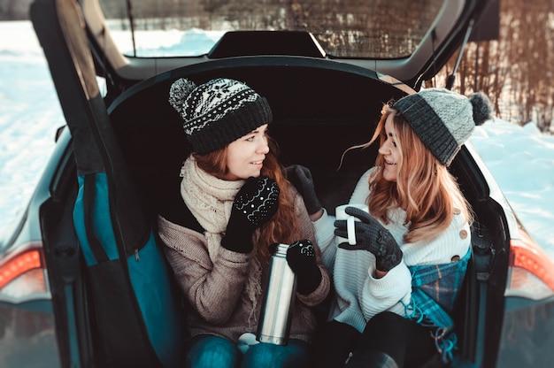 Szczęśliwi przyjaciele w zimowym lesie w samochodzie. dwie szczęśliwe dziewczyny siedzą w bagażniku samochodu i piją kawę z termosu, rozmawiają i śmieją się.