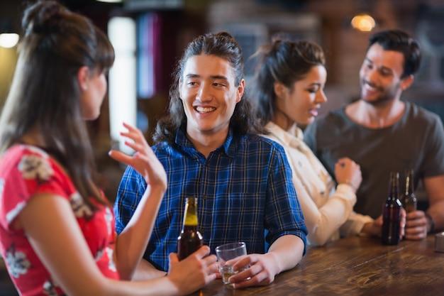Szczęśliwi przyjaciele wchodzący w interakcje przy barze
