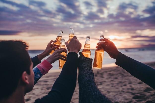 Szczęśliwi przyjaciele wznoszący toast na plaży?