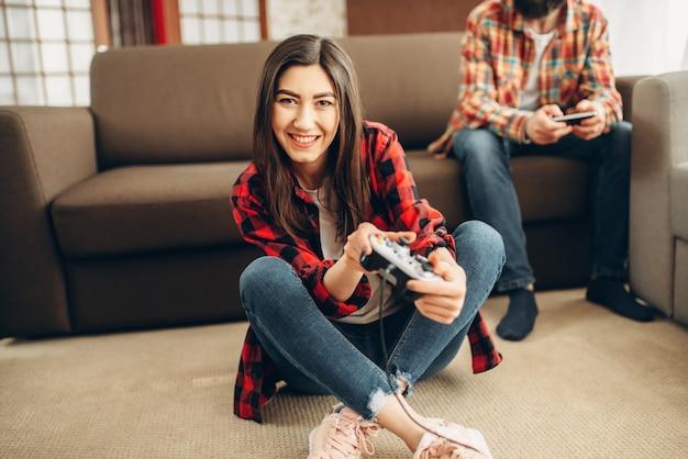 Szczęśliwi przyjaciele z joystickami grają na konsoli wideo