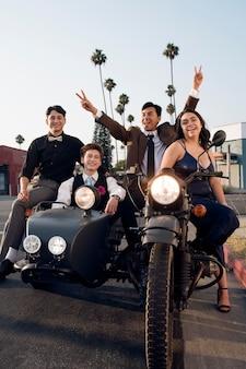 Szczęśliwi przyjaciele z pełnym ujęciem motocykla