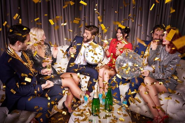 Szczęśliwi przyjaciele z szampanem świętującym