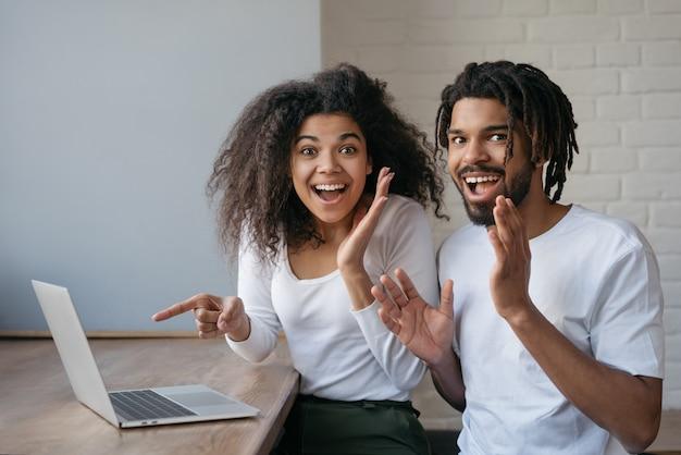 Szczęśliwi przyjaciele zamawiający jedzenie na stronie internetowej, rezerwujący bilety, wskazujący palec na ekranie, siedzący w domu