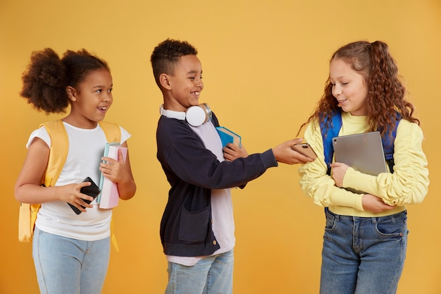 Szczęśliwi przyjaciele ze szkoły, trzymając przybory szkolne