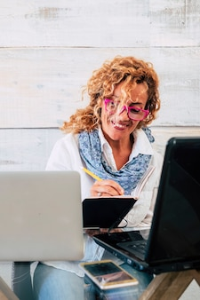 Szczęśliwi, radośni ludzie w pracy z komputerami technologicznymi w stacji roboczej z podwójnym laptopem