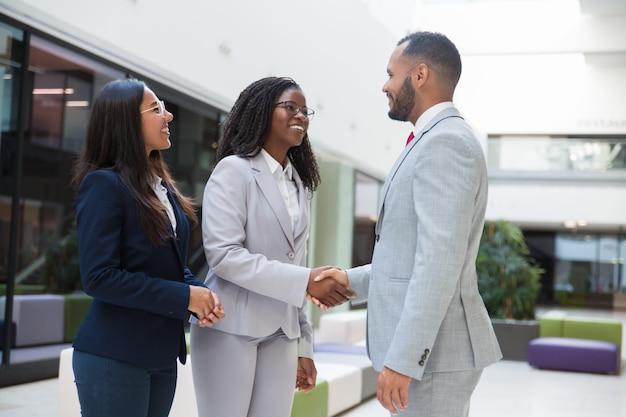 Szczęśliwi radośni różnorodni partnerzy biznesowi witają się