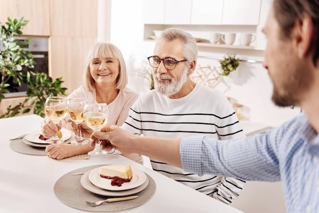 Szczęśliwi razem. charyzmatyczna, optymistyczna, wesoła para w wieku, jedząca kolację i spędzająca weekend ze swoim dojrzałym synem, trzymając kieliszki pełne szampana