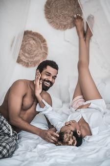 Szczęśliwi razem. ciemnoskóra śliczna kobieta z wysmukłymi nogami i brodym radosnym mężem rozmawiającym o odpoczynku na łóżku w domu
