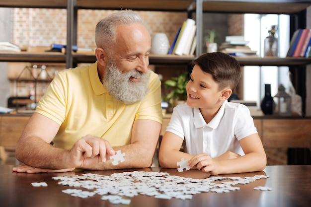 Szczęśliwi razem. miły starszy mężczyzna i jego mały wnuk trzymający kawałki układanki i szeroko się do siebie uśmiechający