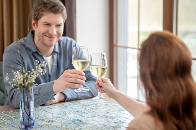Szczęśliwi razem. młody dorosły uśmiechnięty mężczyzna w szarej koszuli wyciąga rękę z kieliszkiem wina w kierunku kobiety siedzącej plecami do kamery