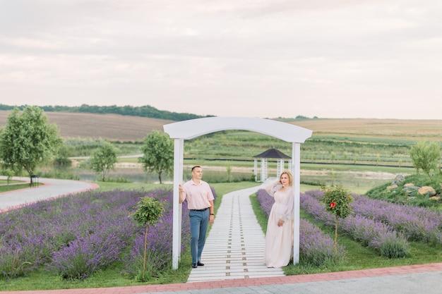Szczęśliwi razem. piękna, stylowa para w średnim wieku na lawendowym polu, stojąca i odwracająca wzrok, oparta na dużym białym drewnianym łuku