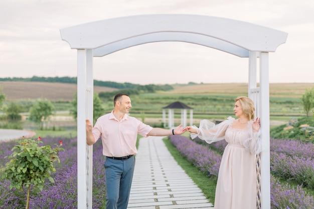 Szczęśliwi razem. piękna stylowa para w średnim wieku w lawendowym polu, stojąc i patrząc na siebie, opierając się na dużym białym drewnianym łuku. portret z bliska