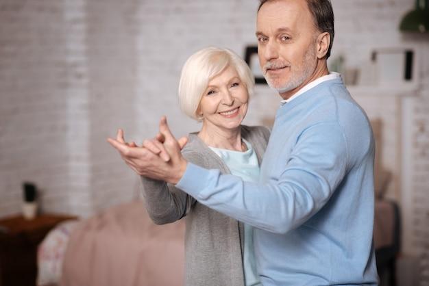 Szczęśliwi Razem. Portret Miły Starszy Mężczyzna I Kobieta Razem Tańczą W Domu. Premium Zdjęcia