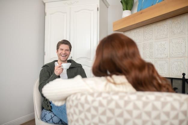 Szczęśliwi razem. roześmiany młody dorosły mężczyzna z kawą i naprzeciwko rudowłosej kobiety plecami do kamery, siedzący w jasnym pokoju przy kominku