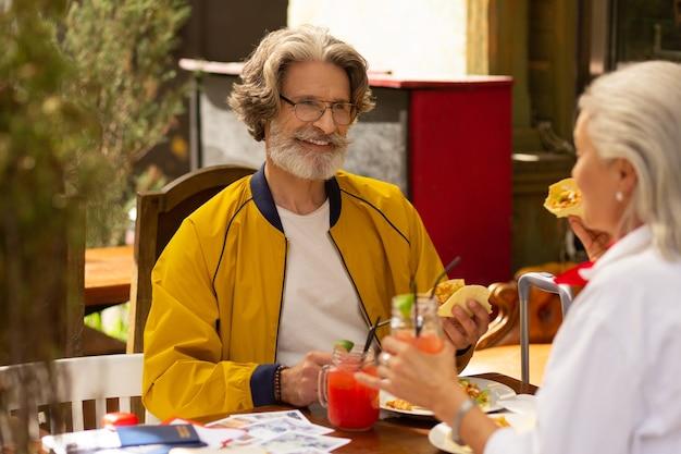 Szczęśliwi razem. wesoły mąż i żona jedzą meksykańskie jedzenie, spędzając czas w miłej ulicznej kawiarni.