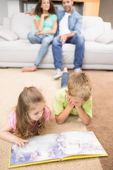 Szczęśliwi rodzeństwa kłama na dywaniku czyta storybook