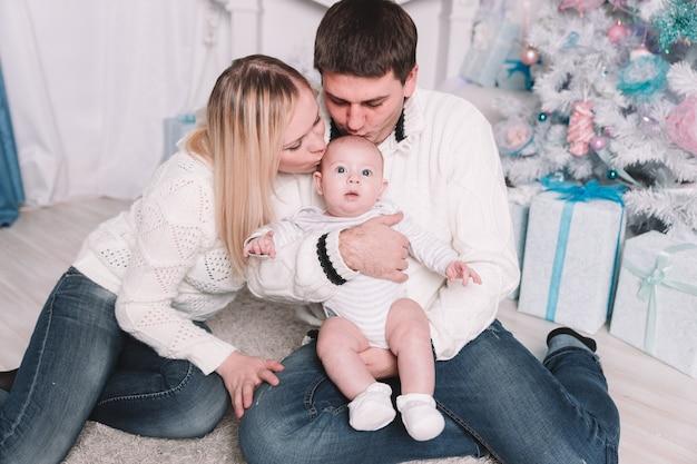 Szczęśliwi rodzice całują swoje dziecko w wigilię bożego narodzenia. pojęcie szczęścia