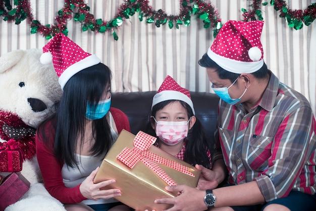 Szczęśliwi rodzice dając świąteczny prezent dla córki z nosić maskę. rodzina w świątecznym wnętrzu