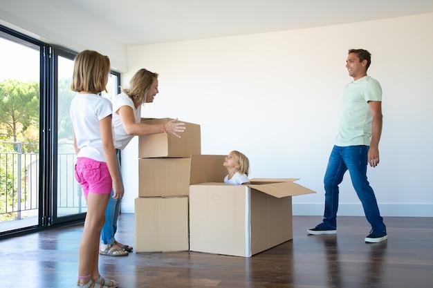 Szczęśliwi rodzice i dwie córki bawią się przy rozpakowywaniu rzeczy w swoim nowym pustym mieszkaniu
