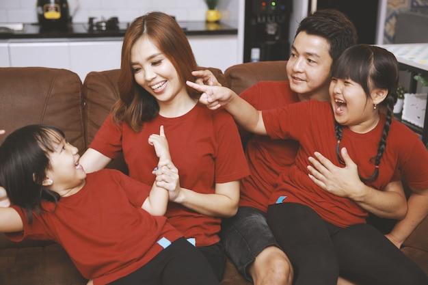 Szczęśliwi rodzice i dzieci bawiące się razem na kanapie wesoła młoda para rozmawiająca i śmiejąca się gra z dwiema małymi córkami w salonie w domu rodzinna aktywność