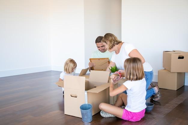 Szczęśliwi rodzice i dzieci rozpakowują rzeczy w nowym pustym mieszkaniu, siadają na podłodze i wyjmują przedmioty z otwartych pudeł