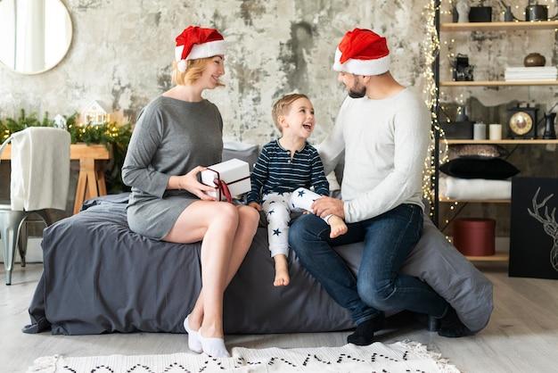 Szczęśliwi rodzice i dziecko, będąc razem w boże narodzenie