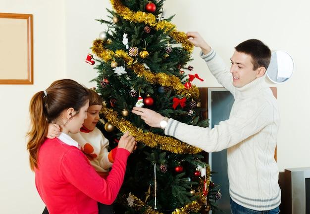 Szczęśliwi rodzice i dziecko dekoruje choinki