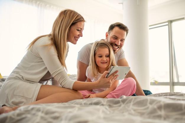 Szczęśliwi rodzice kaukaski śmieją się podczas oglądania ekranu tabletu z ich małą córeczką
