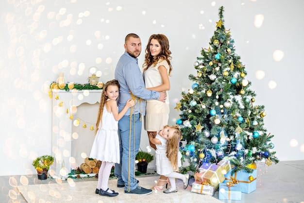 Szczęśliwi rodzice przytulają się z córkami przy białym kominku z elegancką choinką
