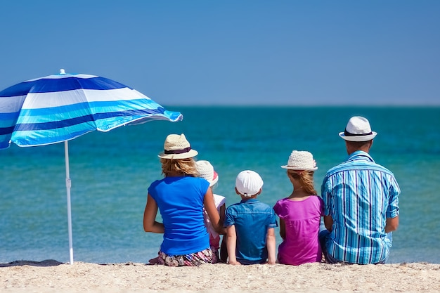 Szczęśliwi rodzice rodziny z dziećmi nad morzem na podróż w naturze