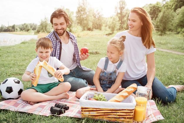 Szczęśliwi rodzice siedzą na kocu ze swoimi dziećmi. wszyscy patrzą, jak mały chłopiec rozdziera chleb. oni się uśmiechają. facet ma w ręku jabłko.