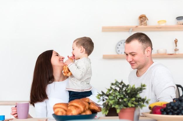 Szczęśliwi rodzice trzyma dziecka w kuchni